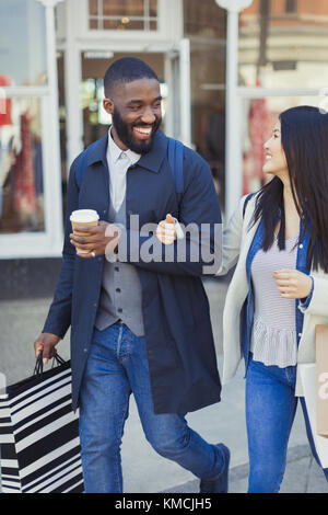 Smiling young couple walking along storefront with coffee and shopping bags - Stock Image