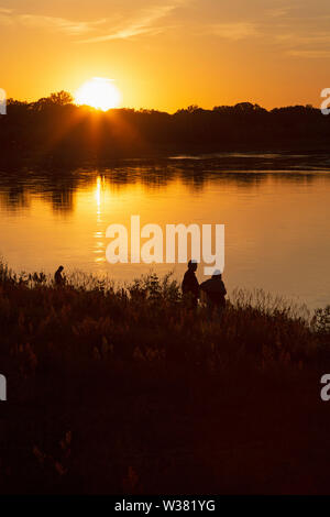 A summer sundown over the River Elbe at Dessau, in Saxony Anhalt, Germany. Trees are siilhouetted alongside the waterway. - Stock Image