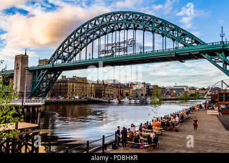 People drinking outside the By The River Brew Co container bars on a summer evening by the Tyne Bridge looking towards Newcastle, Gateshead, UK. - Stock Image