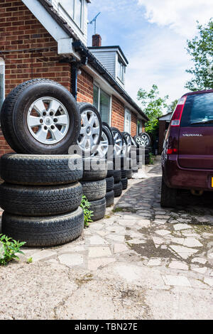 A row of wheels and tires stacked in sets outside a building at a car breakers scrapyard - Stock Image