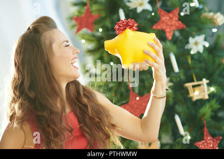 happy trendy woman in red dress with yellow piggy bank near Christmas tree - Stock Image
