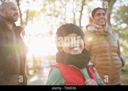 Portrait happy boy with parents in sunny autumn park - Stock Image