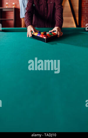 Close-up of billiards player arranging balls on table - Stock Image