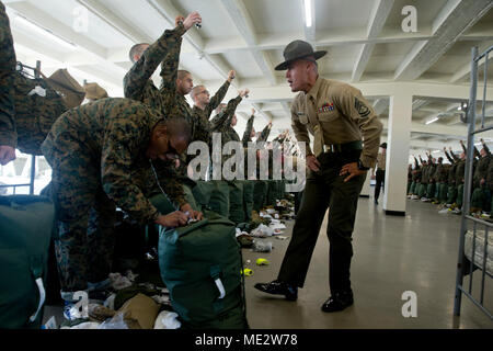Gunnery Sgt. Mark A. Sanchez, drill instructor, Golf Company, 2nd Recruit Training Battalion, instructs a recruit to follow directions during pick up at Marine Corps Recruit Depot San Diego, Dec. 15. During the first few hours the drill instructors are with their new recruits they will teach them the in-house procedures they must follow for the rest of recruit training. Annually, more than 17,000 males recruited from the Western Recruiting Region are trained at MCRD San Diego. Golf Company is scheduled to graduate March 9. - Stock Image