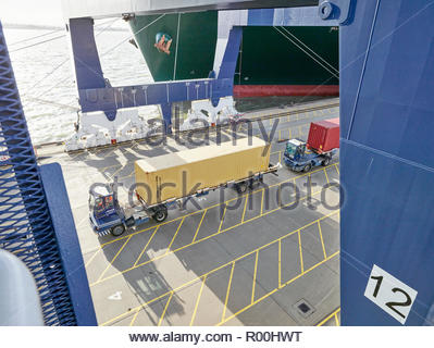 Truck with cargo container driving on dock - Stock Image