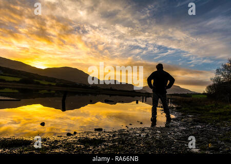 Ardara, County Donegal, Ireland. 1st January 2019. A walker takes in the first sunset of the year which is reflected in a still lake. Credit: Richard Wayman/Alamy Live News - Stock Image