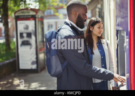 Young couple using urban ATM - Stock Image