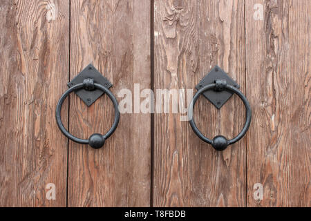 Oak doors with wrought iron handles in the form of rings - Stock Image