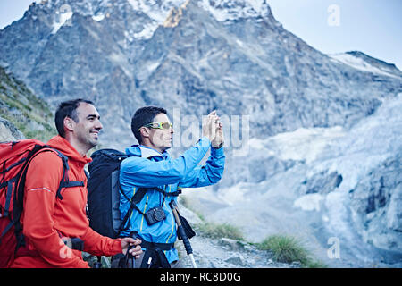 Hikers taking photograph, Mont Cervin, Matterhorn, Valais, Switzerland - Stock Image