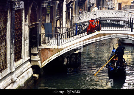 Europe, Italy, Venice Carnival. Canal and gondola. Two revelers on a bridge - Stock Image