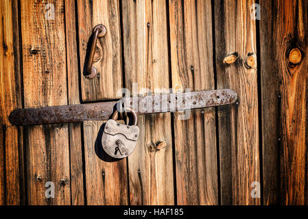 Old vintage metal industrial style hinge on faded textured wood. The wood is brown with grains and patterns due - Stock Image