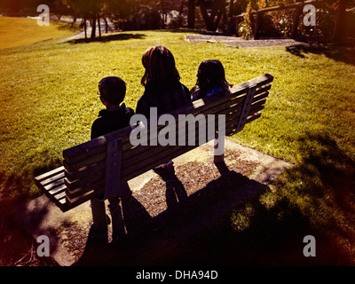 Mother, son and daughter sit on park bench on sunny winter day - Stock Image