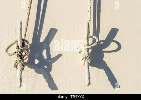 Two nautical ropes tied with marine knots to metal cleats on white exterior wall of cruise ship in morning sunlight. - Stock Image