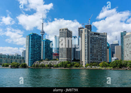 View of the CN Tower and surrounding downtown Toronto buildings seen from Lake Ontario, crossing to Toronto Island on the ferry on a sunny day. - Stock Image