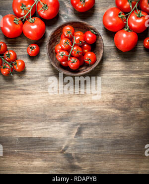 Ripe tomatoes in a bowl . On a wooden table. - Stock Image
