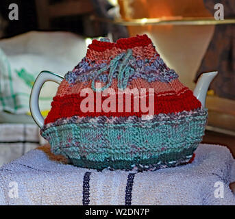 A hand knitted tea cosy in orange, green and red shades of yarn that is in use on a large tea pot.  The tea cosy has a draw string around the top. - Stock Image
