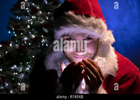 Good looking male santa smiling and holding lights in his hands in front of christmas tree and looking at camera - Stock Image