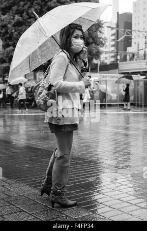 Woman wearing mask and carrying umbrella stands in the rain at the beginning of autumn in Shibuya, Tokyo - Stock Image