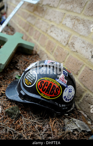 Construction worker's safety helmet covered in pro-Union stickers. - Stock Image