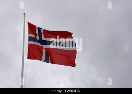 national norwegian flag is blowing in the wind in front of dark cloudy sky with copy space, norwegian flag on flagpole at cloudy day - Stock Image
