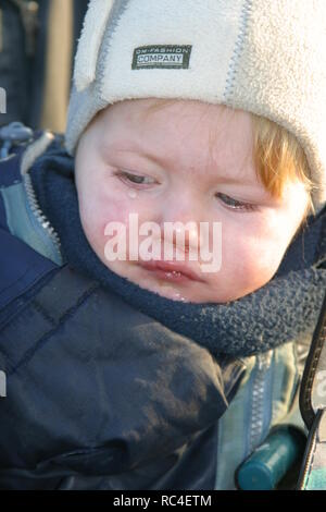 Close-up sick little baby boy outside with a woolen hat, has a cold - Stock Image