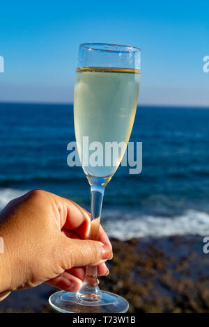 Hand holding glass of Champagne, prosecco or cava, outside terrace with sea view close up - Stock Image
