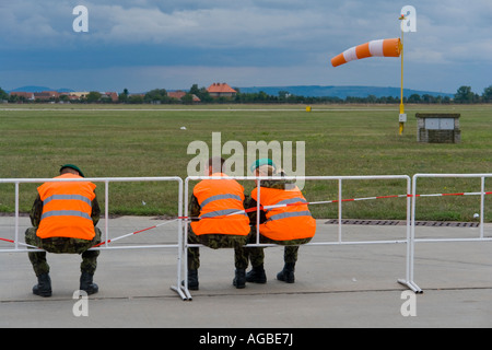 Brightly dressed guards resting after airshow event with blown air sock in background - Stock Image