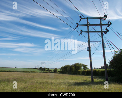 Electricity pylons running through mixed arable farm land with hedge and hedgerow and blue sky. Oxfordshire - Stock Image