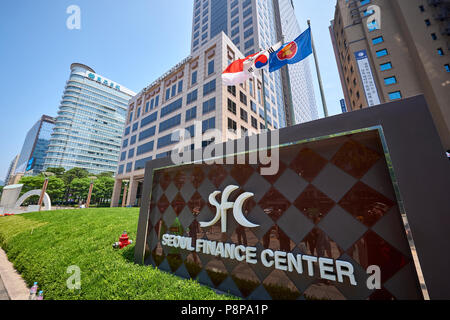 Low angle shot of Seoul Finance Center entrance sign in Seosomun-dong, Seoul, South Korea, with South Korean flag in the background. - Stock Image