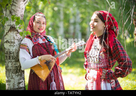 Two young woman in traditional russian clothes standing in the forest. One of them holding balalaika. Vertical shot - Stock Image