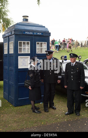 Chichester, West Sussex, UK. 13th Sep, 2013. Goodwood Revival. Goodwood Racing Circuit, West Sussex - Friday 13th September. Three police officers (actors) stand outside of a blue police box in a themed area of the festival. © MeonStock/Alamy Live News - Stock Image