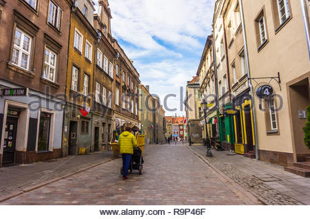 Poznan, Poland - November 12, 2018: Man with child buggy walking on a street leading to the old city square. - Stock Image