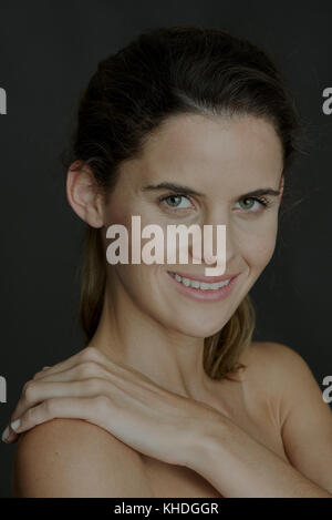 Young woman with hand on bare shoulder, smiling, portrait - Stock Image