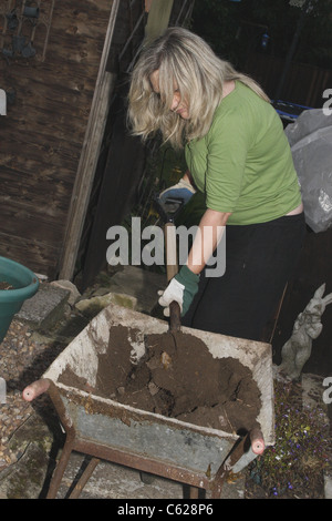 woman using spade to move soil from wheelbarrow to tubs - Stock Image