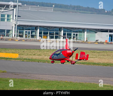 A Small two seat Gyrocopter returning from a flight across the Moray Firth to the Black Isle - Stock Image