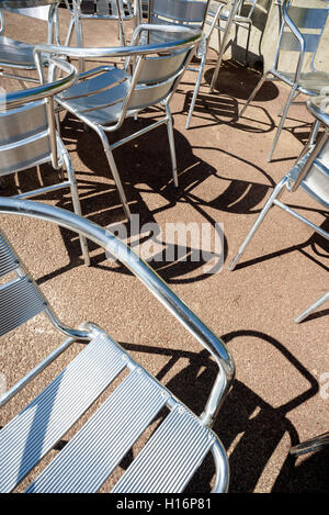 Metal deck chairs cast shadows on the floor in the height of the summer sun. - Stock Image