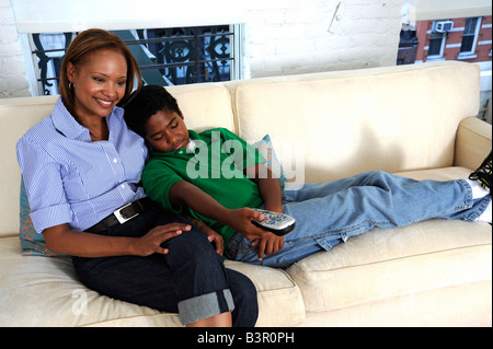 Smiling African American mother and son watching TV on the couch - Stock Image