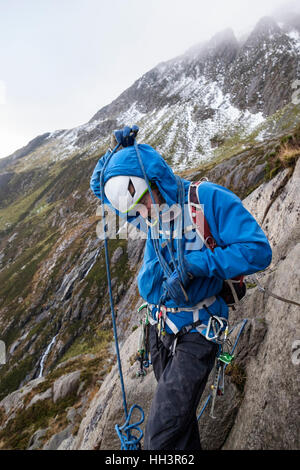 A mountain climber coiling a climbing rope around his body preparing to lead a rock scramble in Cwm Idwal, Ogwen, - Stock Image
