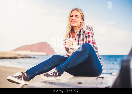 Cheerful beautiful blonde tourist sit down on her black car and enjoy the outdoor activity feeling the nature - young traveler people with ocean and m - Stock Image