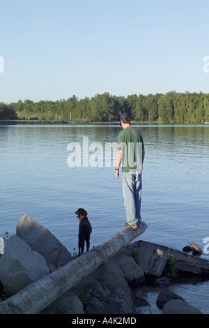 Dog and his owner looking out on lake Champlain, North Hero, Vermont in summer. - Stock Image