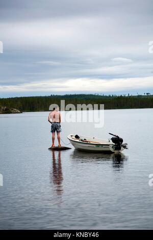 Man standing on a rock out on the lake, countryside of northern Sweden. - Stock Image