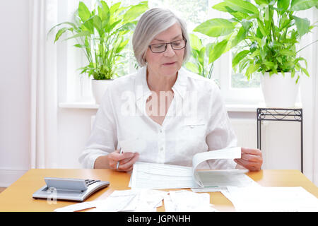 Senior german woman at home with a calculator and lots of bills and receipts, filling out the printed forms of the - Stock Image