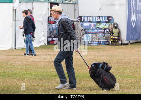 A man pulling a suitcase at a festival - Stock Image
