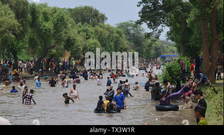 Lahore, Pakistan. 23rd June, 2019. A large number of Pakistani people taking a bath in the canal water to beat the heat and get some relief from the extremely hot weather during the summer season in Lahore. The temperature reached 42 degrees Celsius (108 Fahrenheit), Many cities in Pakistan are facing heat wave conditions with temperatures reaching 49 degrees Celsius (120.2 Fahrenheit) in some places. Credit: Rana Sajid Hussain/Pacific Press/Alamy Live News - Stock Image