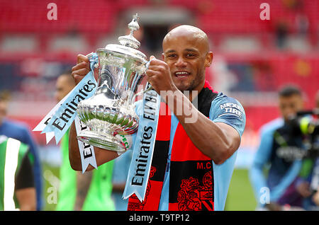 Manchester City's Vincent Kompany lifts the trophy after his side win the FA Cup Final at Wembley Stadium, London. - Stock Image