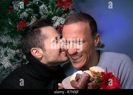 Male gay couple kissing, smiling, laughing in front of christmas tree with plate of cakes - Stock Image