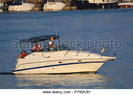 Littlehampton, UK. Sunday 8th July 2018. People take a late evening boat trip on the River Arun, on a very warm evening in Littlehampton, near the South Coast. Credit: Geoff Smith / Alamy Live News. - Stock Image