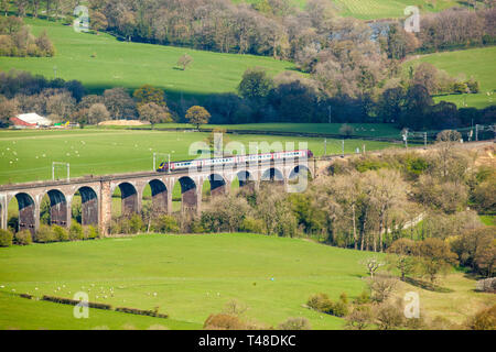 Electric train on the railway over the viaduct bridge on the Cheshire plain near Bosley Congleton Cheshire England seen from bosley cloud or cloud end - Stock Image