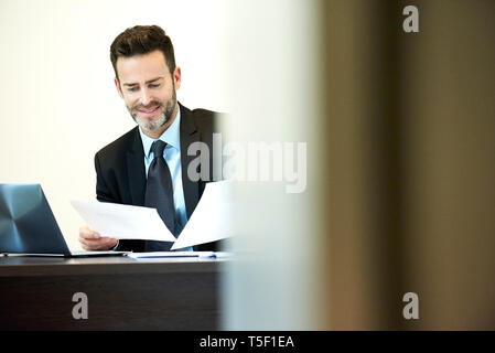 Businessman reading documents in office - Stock Image