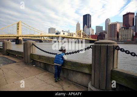Boy gazing at the Allegheny River and city skyline, Pittsburgh, PA, USA - Stock Image